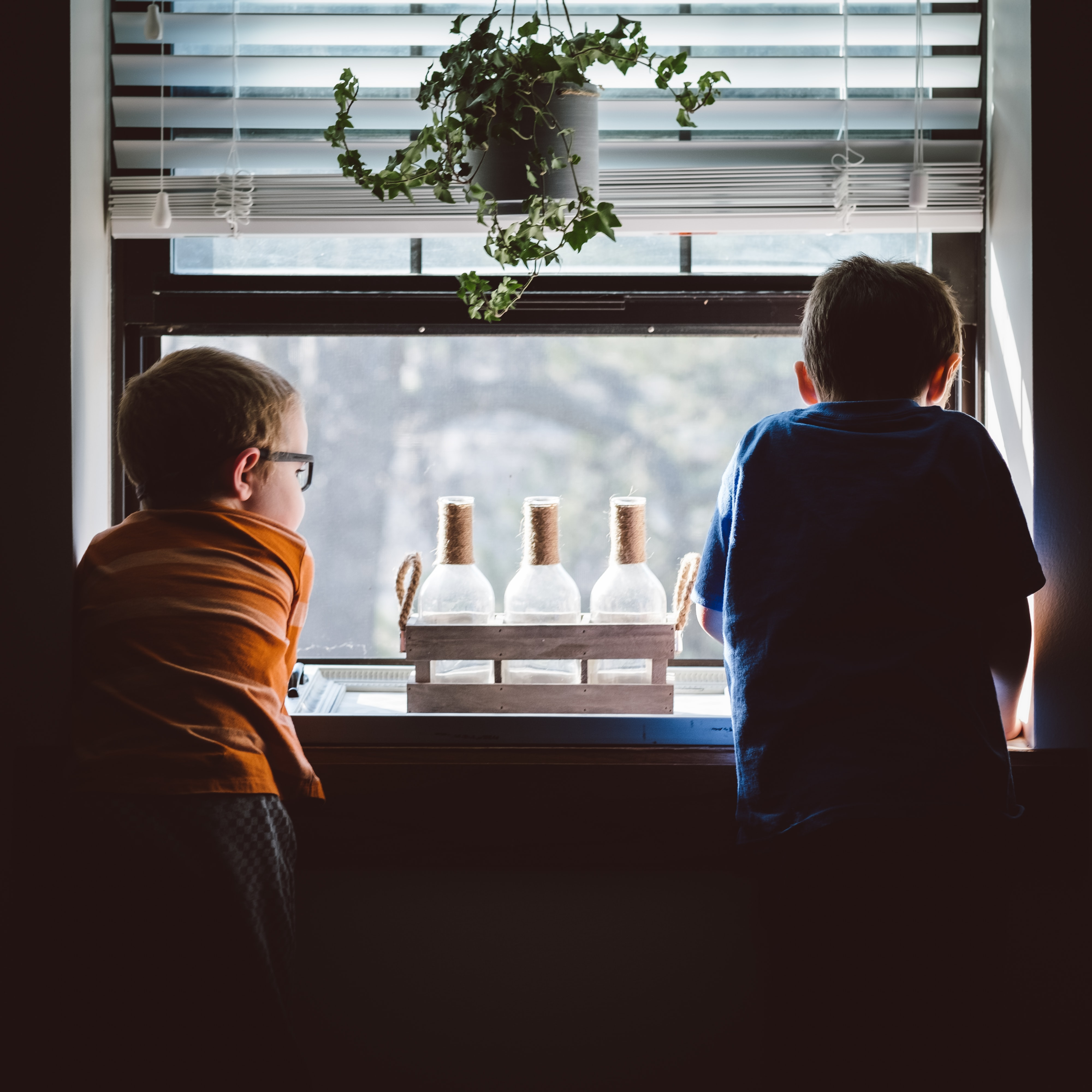 two kids watching outside while staying at home